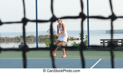 Girl play tennis outdoor on tennis court. Dolly