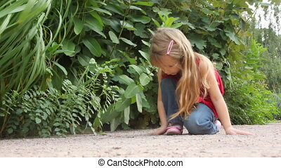 girl play with sand near some plants