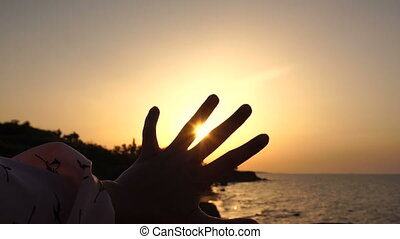 Girl Play with the Rising Sun At the Sea at Dawn Time. Handling Sun Rays Between Fingers.