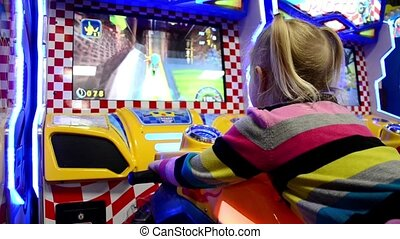 Girl playing arcade game machine at an amusement park