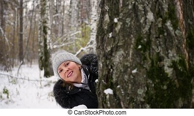 girl playing by throwing snowballs from behind tree in the winter Park