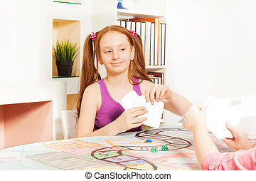 Girl playing cards sitting at the gaming table