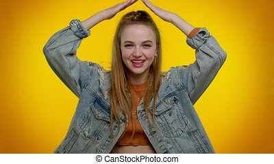 Pretty stylish teen girl playing childish catching up game, feeling in safe making roof above head with hands, insurance, security service. Young woman. Indoor studio shot on yellow wall background