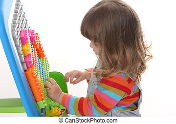 girl playing colorful building toy blocks