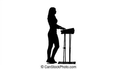 Girl playing fast music synthesizer, silhouette on a white background, in the half turn plays the piano, in full growth, nice moves to the music, dancing musician, studio, white background