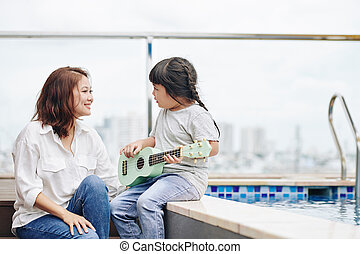 Girl playing for mother
