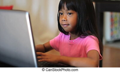 Girl Playing Games On A Lap Top - A cute little Asian girl...