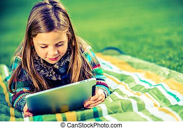 Girl Playing Games on Her Tablet Device While Laying on the...