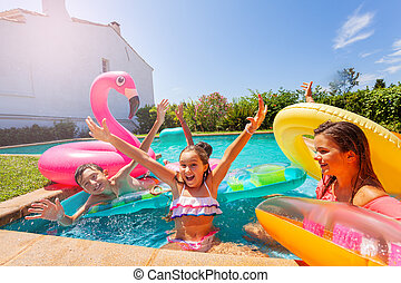 Girl playing games with friends during pool party