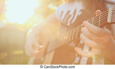 Girl playing guitar in nature