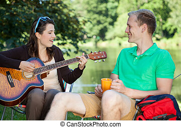 Girl playing guitar on a camping