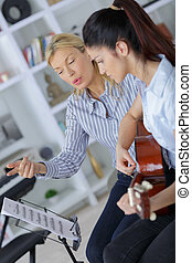 girl playing guitar with her mum