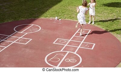 Girl playing Hopscotch - Little girl jumping while playing...