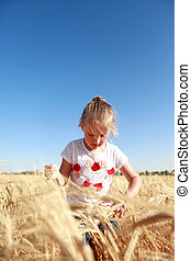 girl playing in a field of wheat