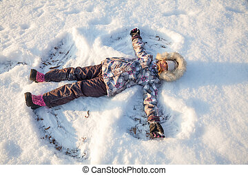 Girl playing in a snow enjoying winter