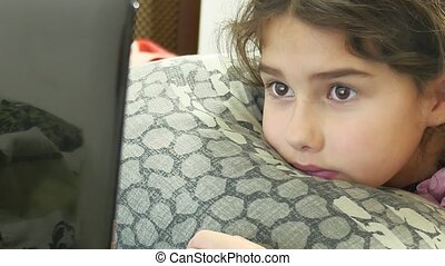 girl playing in laptop lying on bed, online games
