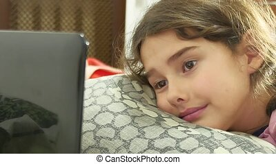 girl playing in laptop lying on the bed, online games
