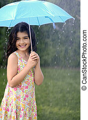 girl playing in rain with umbrella