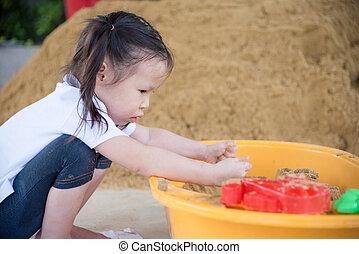 girl playing in sandbox