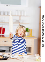Girl playing in the kitchen holding a rolling-pin