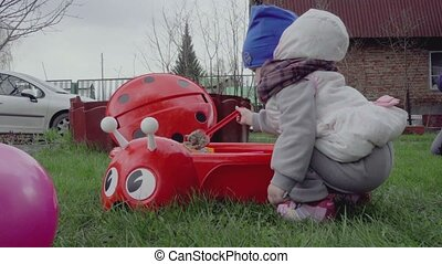 Girl playing in the sandbox on the lawn