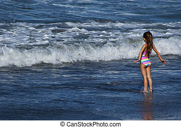 girl playing in the surf