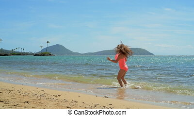 Girl playing in water at the beach 4k