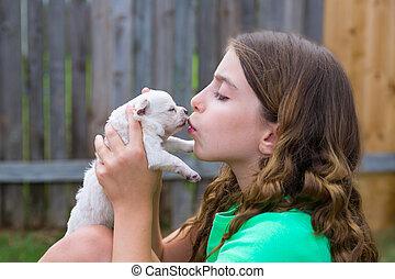 Girl playing kissing puppy chihuahua pet dog