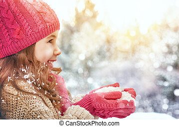 girl playing on a winter walk - happy child girl plaing on a...