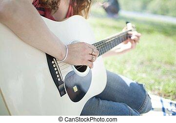 Girl playing on guitar.