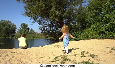 Girl playing on shore near mother - Girl walking on sandy...