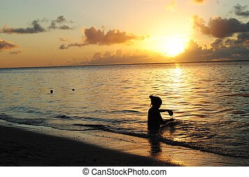 Girl playing on the beach at sunset