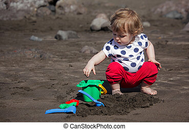 Girl playing on the beach with volcanic sand