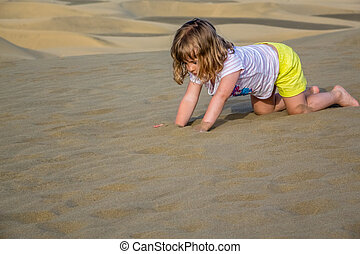 Girl playing on the sand dunes