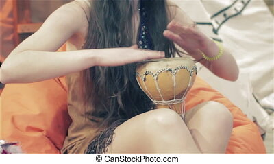 Girl playing on traditional Indian tabla drums close up