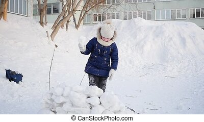 girl playing outdoors in winter. Children throw snowballs