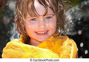 Girl playing outside with water on the summer