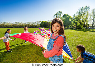 Girl playing parachute game on the green field