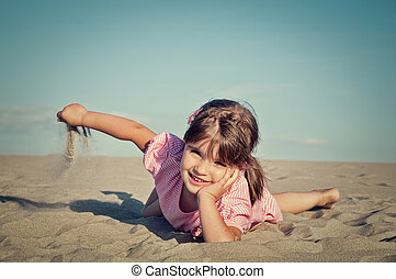 girl playing sand at the beach