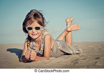 girl playing sand at the beach.