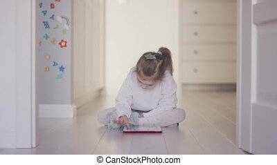Girl playing tablet on floor at home - Casual little girl...