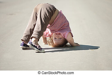 girl playing upside down in street