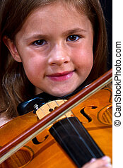 Girl playing violin in pink dress concentration on black