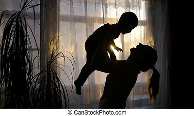 girl playing with a baby near window.