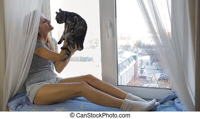 Girl playing with a British cat