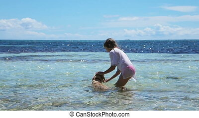 Girl playing with a dog on the beach