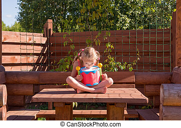 girl playing with a drum in wooden arbor