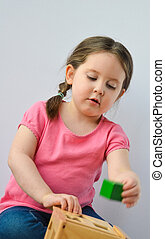Girl playing with a wooden shapes