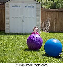Girl Playing with Ball in Backyard
