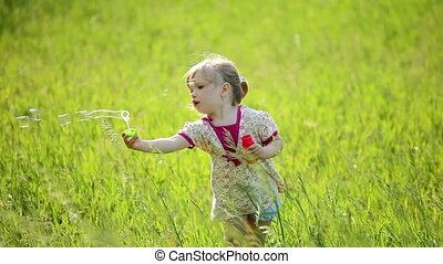 Girl playing with bubbles and wind